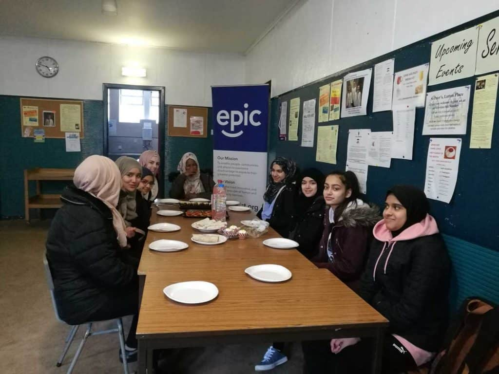 The Girls from EGP sit at a table which is holding a feast