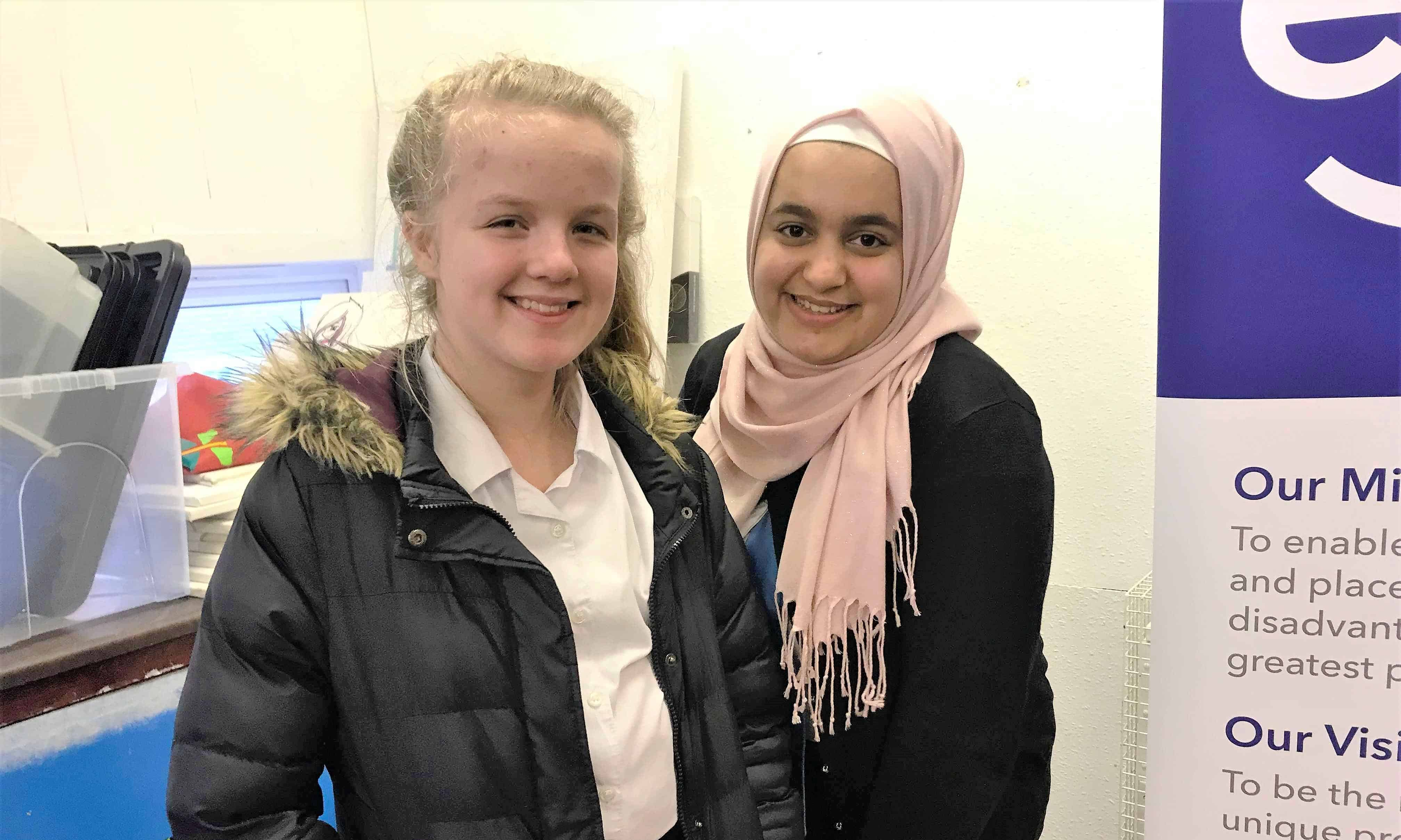 Eilidh and Amal, two girls from different religious backgrounds, stand side-by-side.