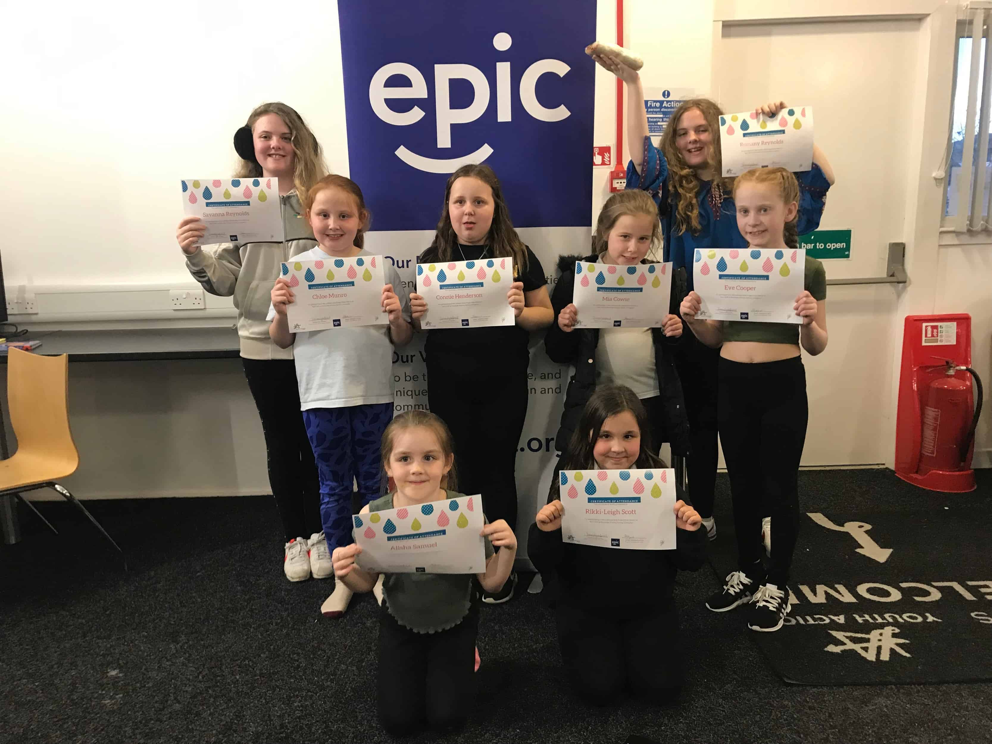 8 girls from the Livingston Girls Project pose with their certificate.