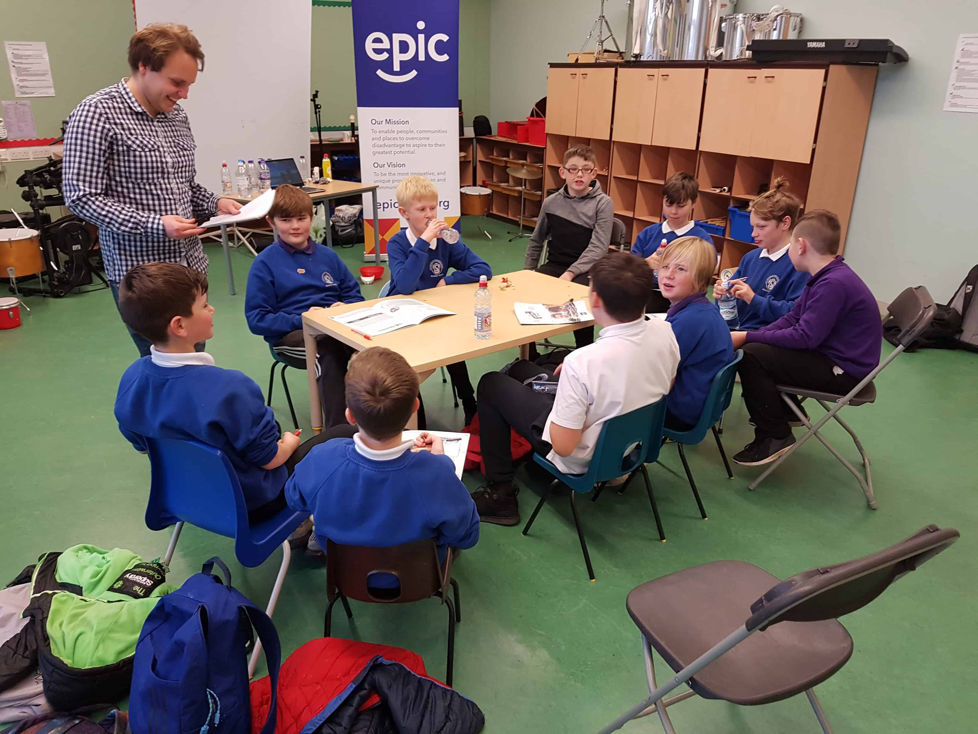 A group of boys from the Tranent Boys Project sit around a table working through booklets.