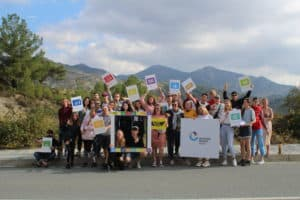 A group of youth stand together in front of a mountain in Cyprus, waving colourful signs and posters.