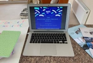 "A laptop is open and features a blue slide with blue and cream confetti. The text on the slide says: ""Scottis Girls Project - Level 2. Online booklet in partnership with EPIC Assist Scotland."""